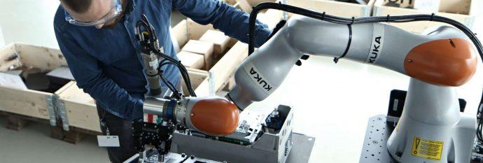 Mand arbejder med cobot til produktions samlebånd